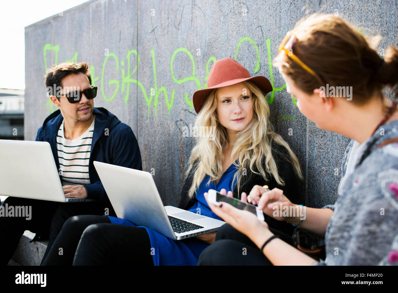 Friends talking while doing freelance work outdoors - Stock Image