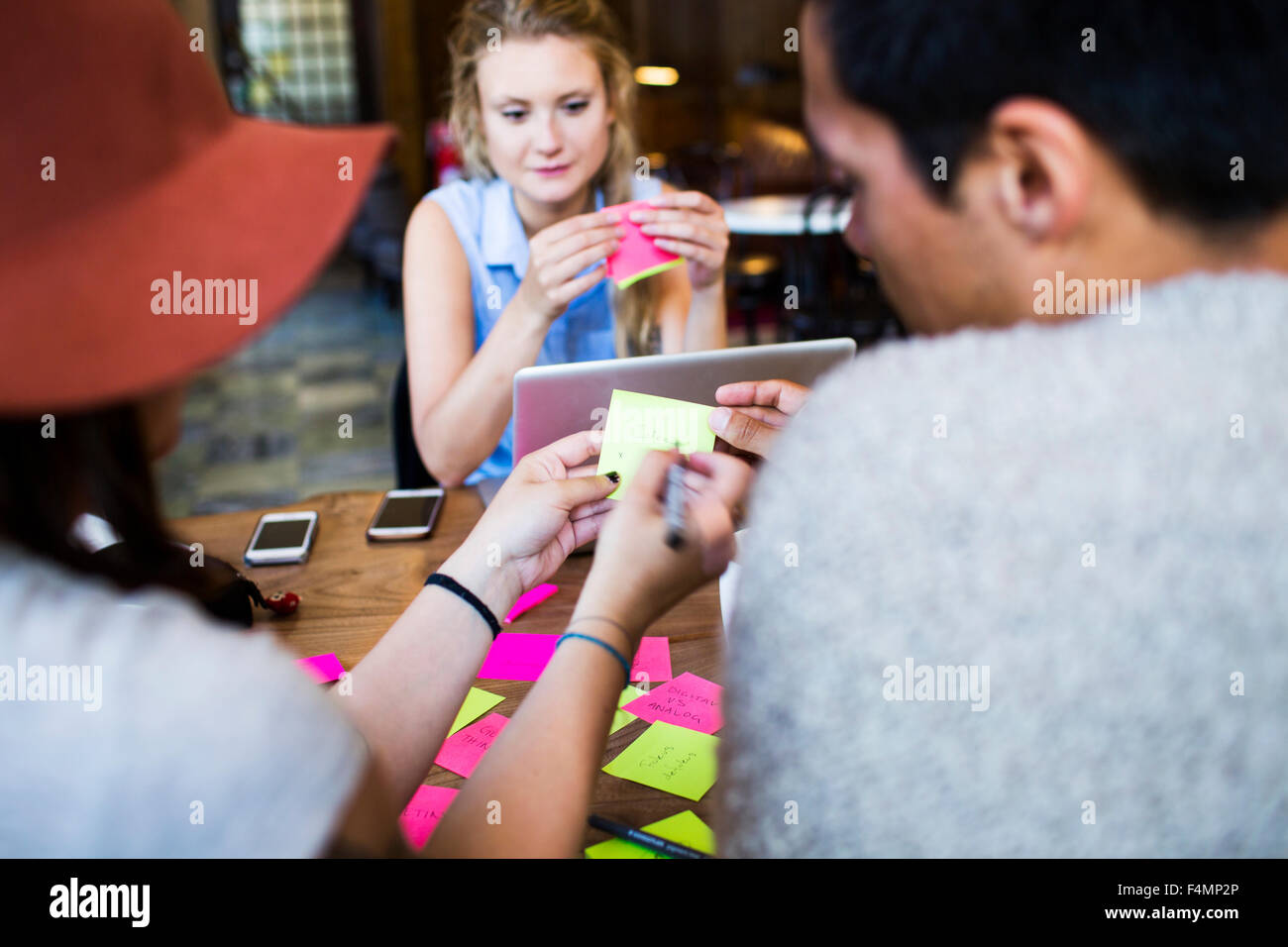 Friends writing on adhesive note while doing freelance work at cafe - Stock Image