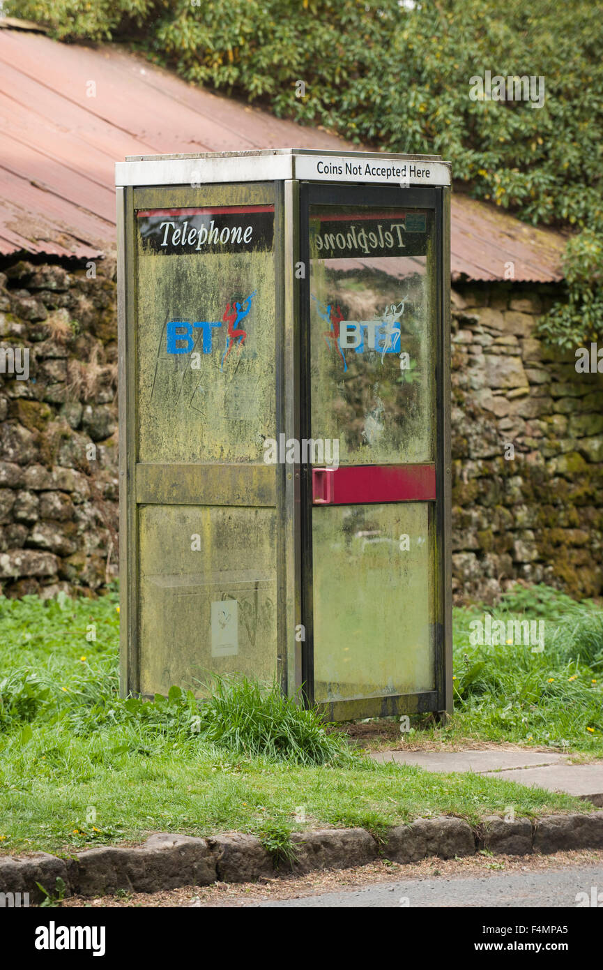 A KX100 telephone box at the roadside in rural North Yorkshire, England, UK.  This kiosk has dirty, mud-splashed - Stock Image