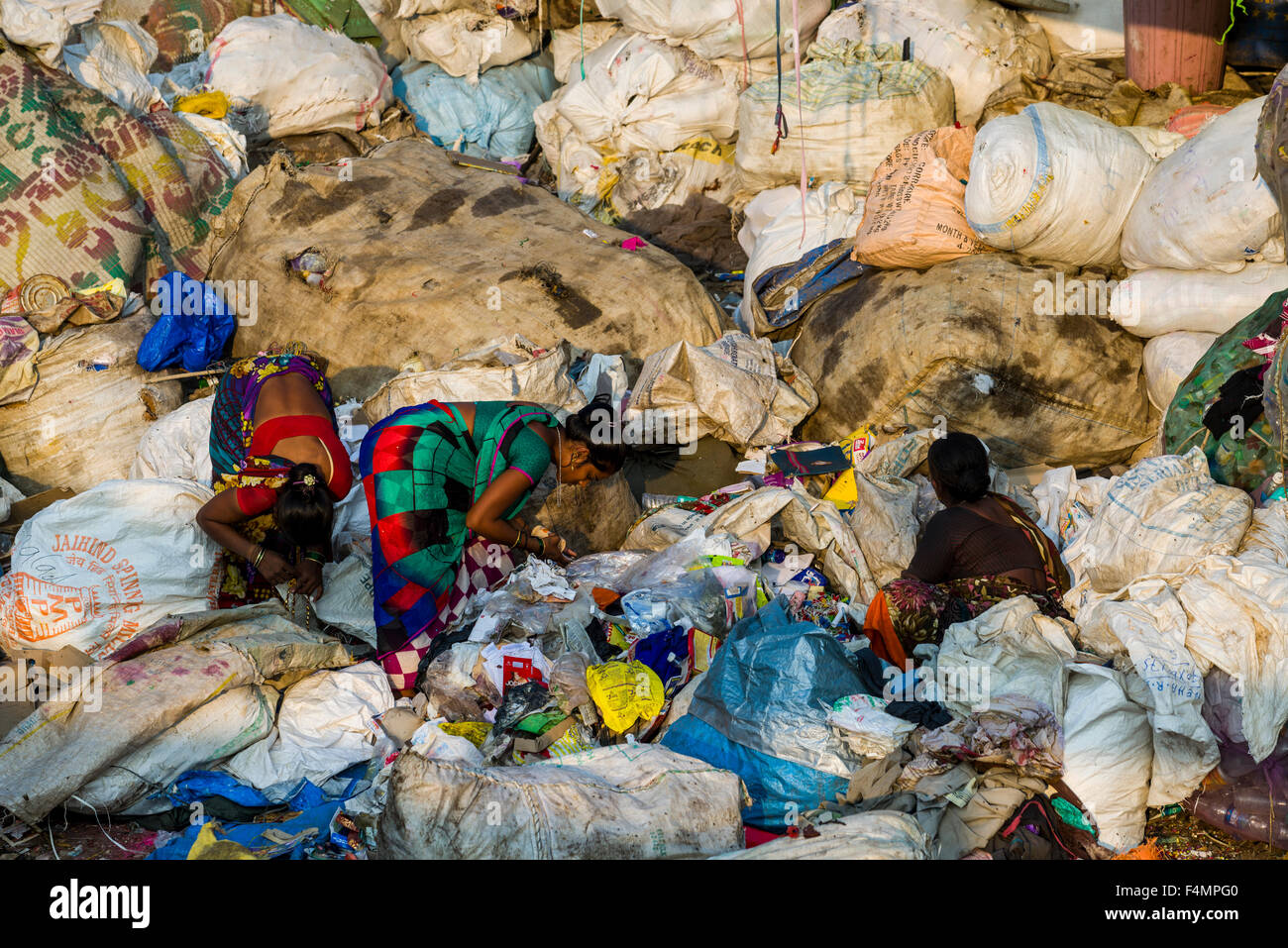Two women in colorful saris are sorting out garbage. About 10.000 labour are working in 800 little companies, mainly in the garb Stock Photo
