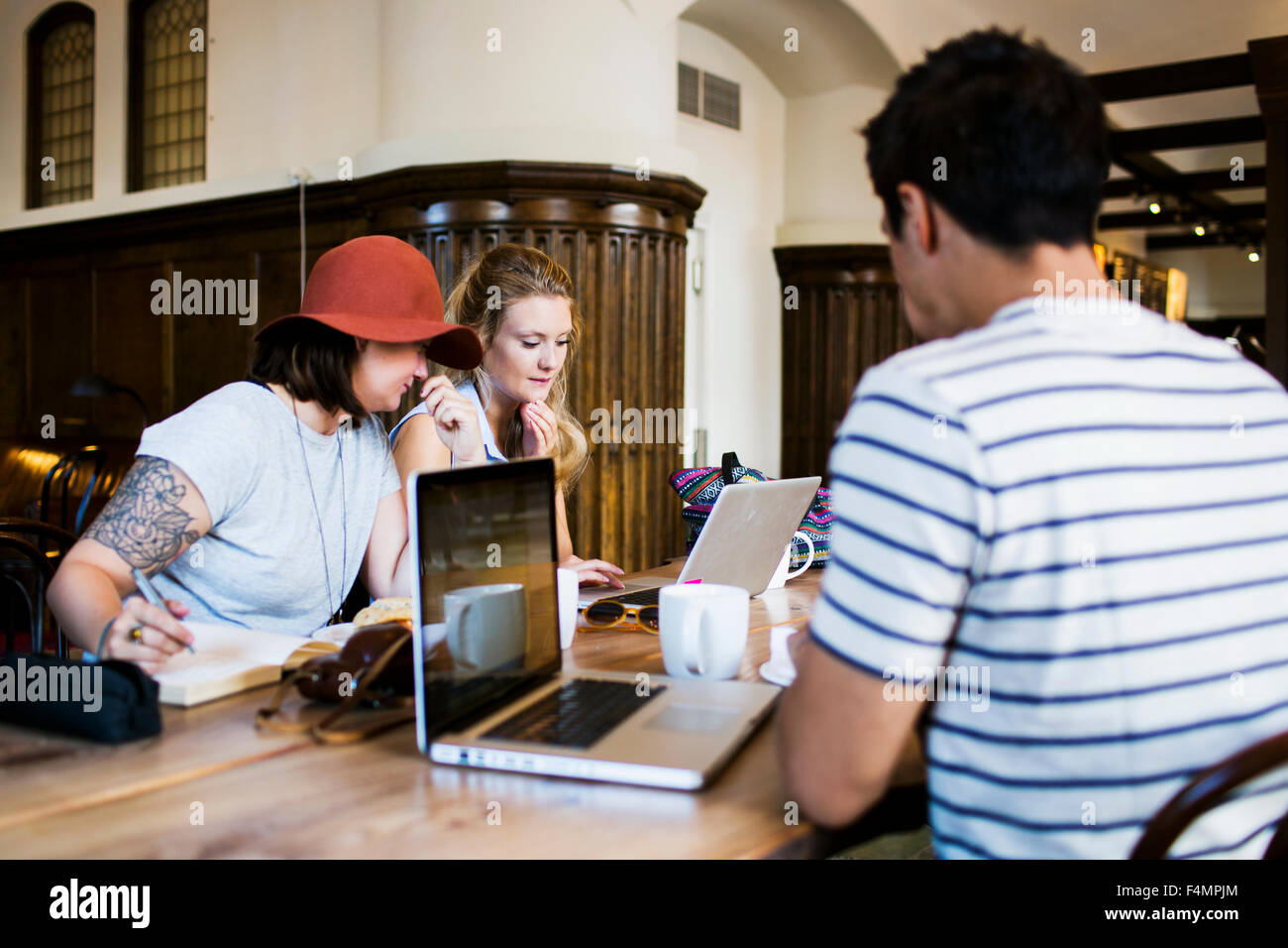 Friends doing freelance work at cafe table - Stock Image