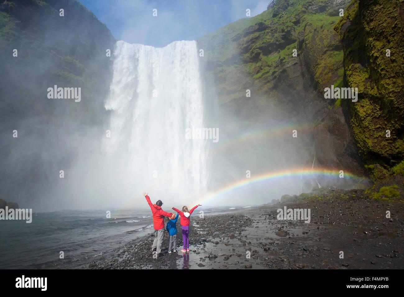 Family in the rainbow beneath 60m-high Skogafoss waterfall, Skogar, Sudhurland, Iceland. - Stock Image