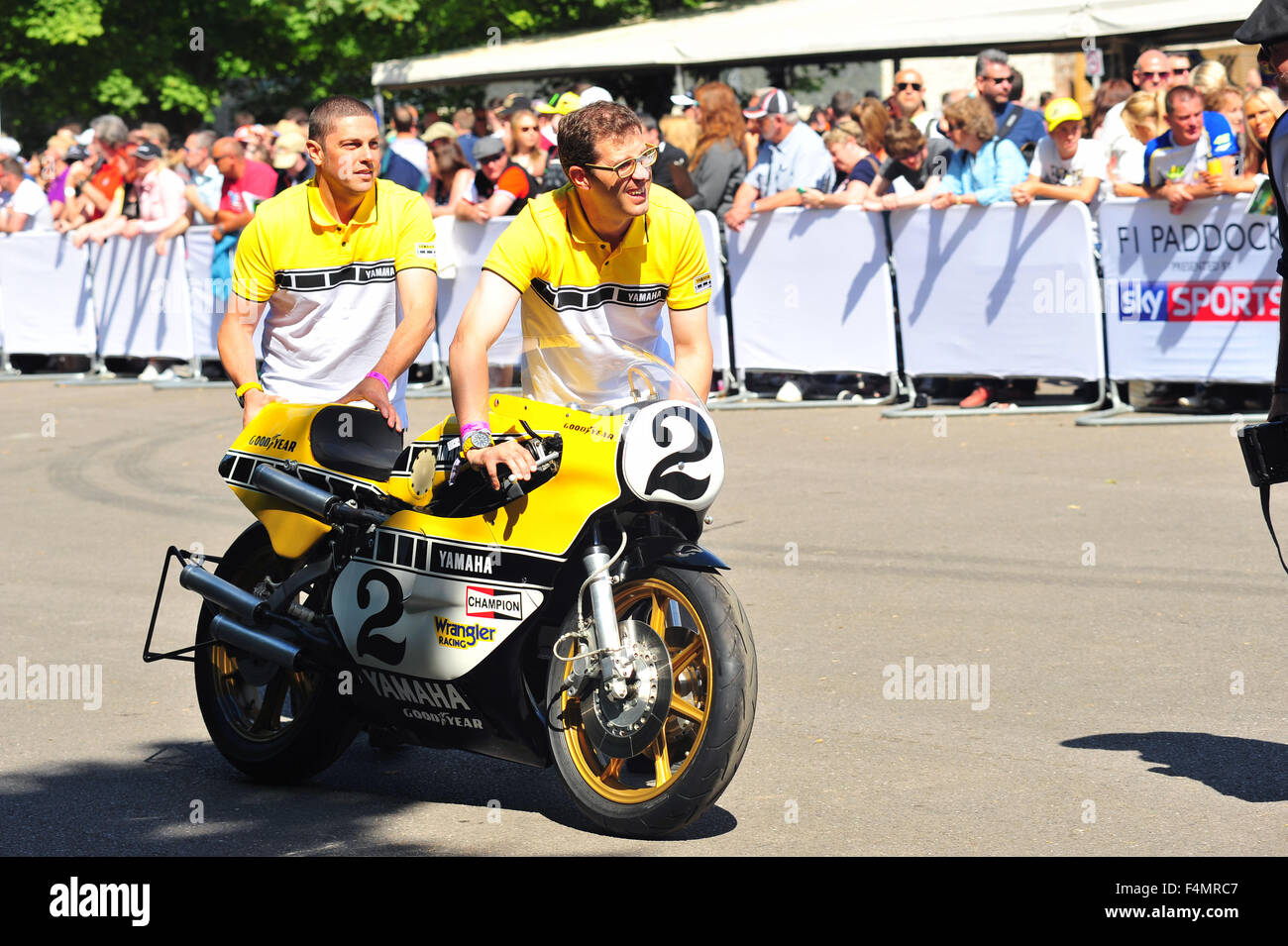 Yamaha technicians push a Yamaha YZR750 OW31 racing bike into the paddock at the Goodwood Festival of Speed in the - Stock Image