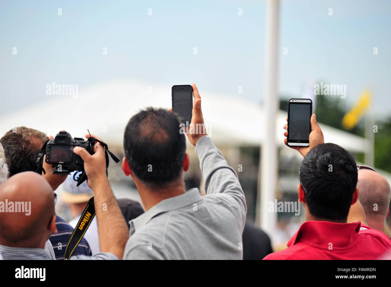 The crowd use cameras and smartphones to take photos at the Goodwood Festival of Speed in the UK. - Stock Image