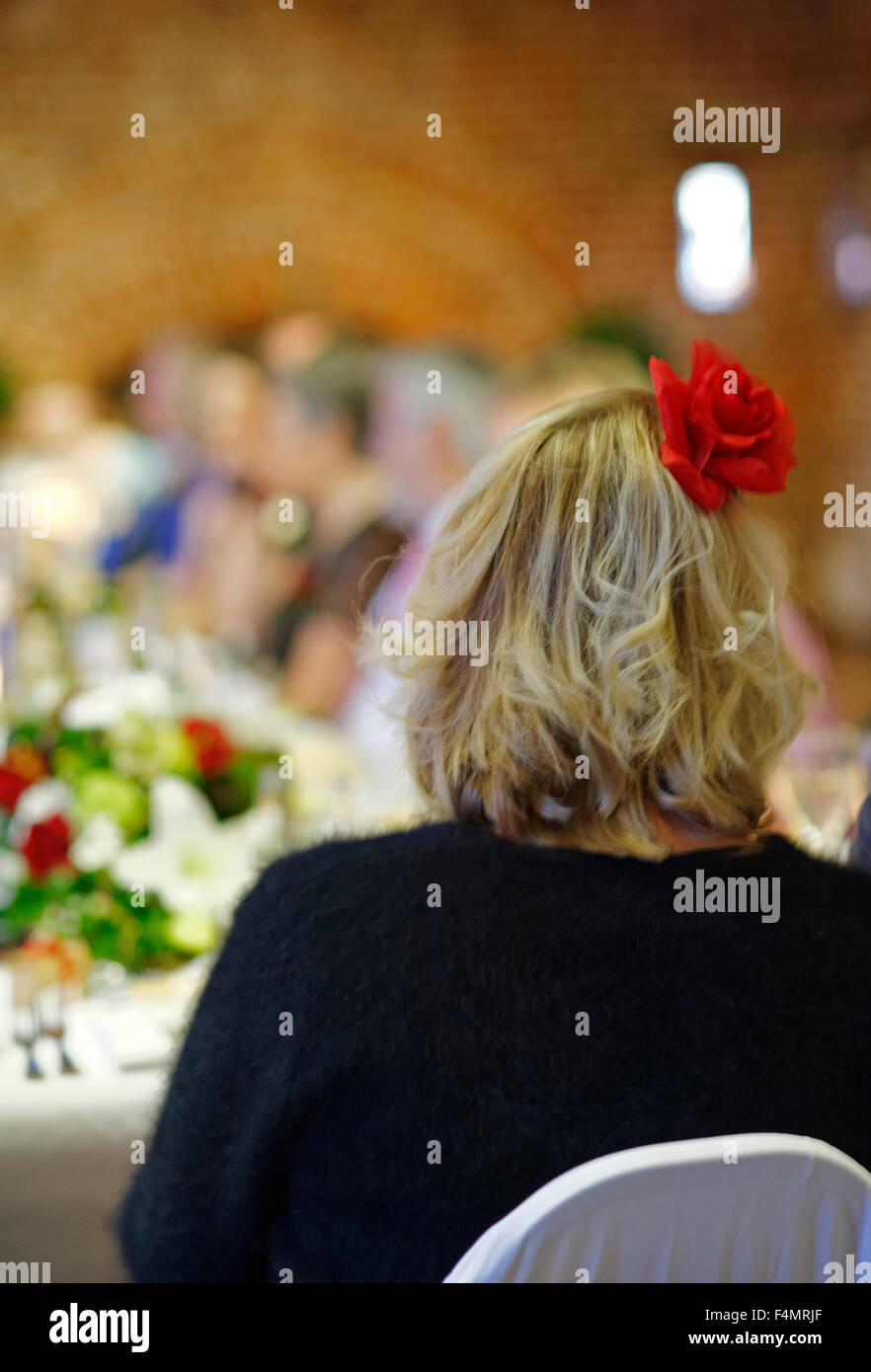 Woman sitting at a wedding dinner - Stock Image