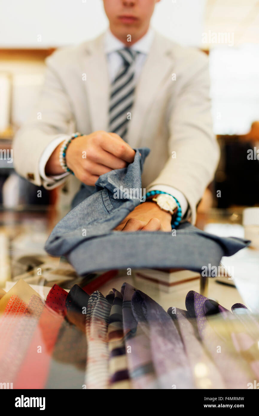 Sales clerk folding shirt on table in clothing showroom - Stock Image