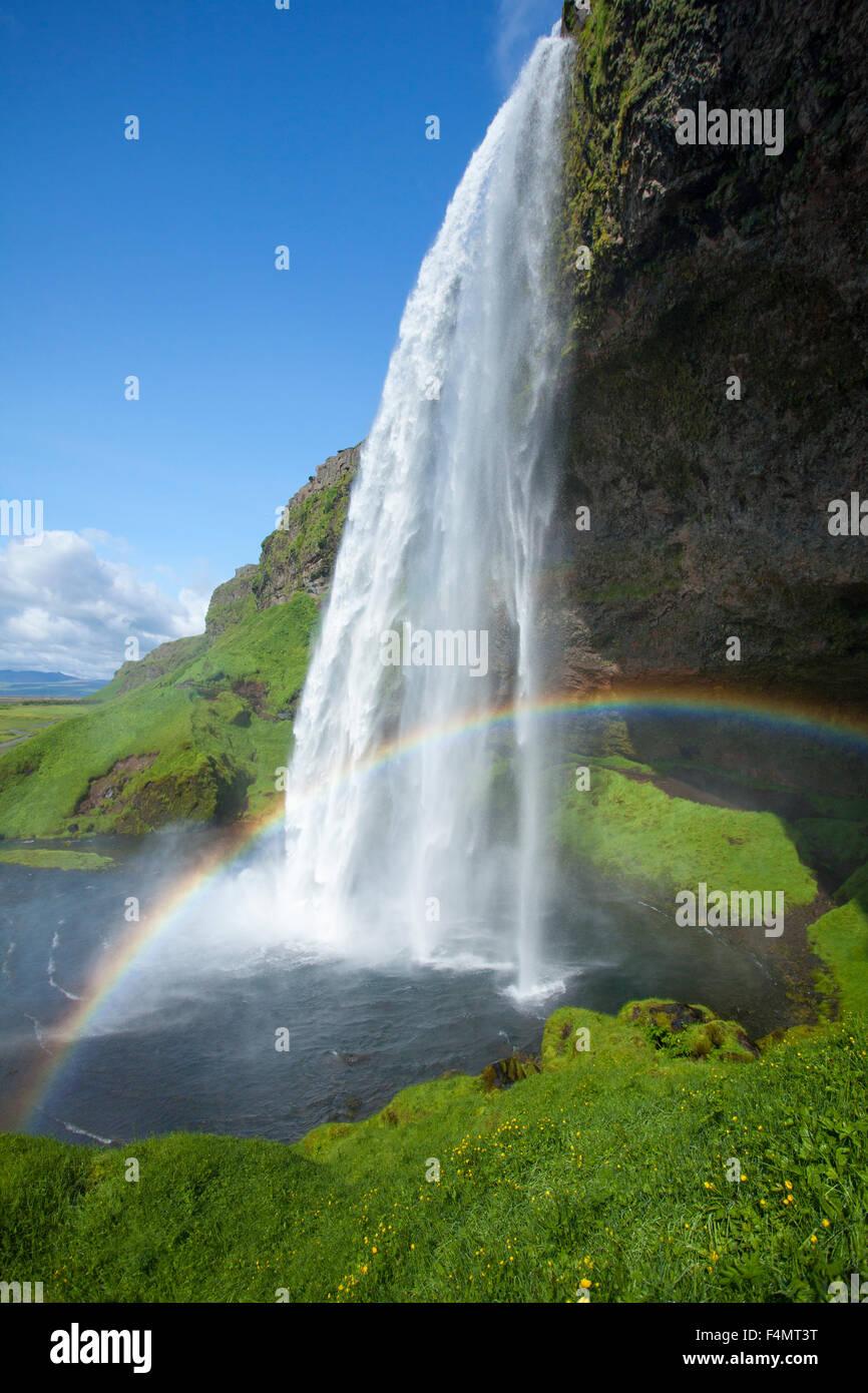 Rainbow beneath 60m-high Seljalandsfoss waterfall, Sudhurland, Iceland. - Stock Image