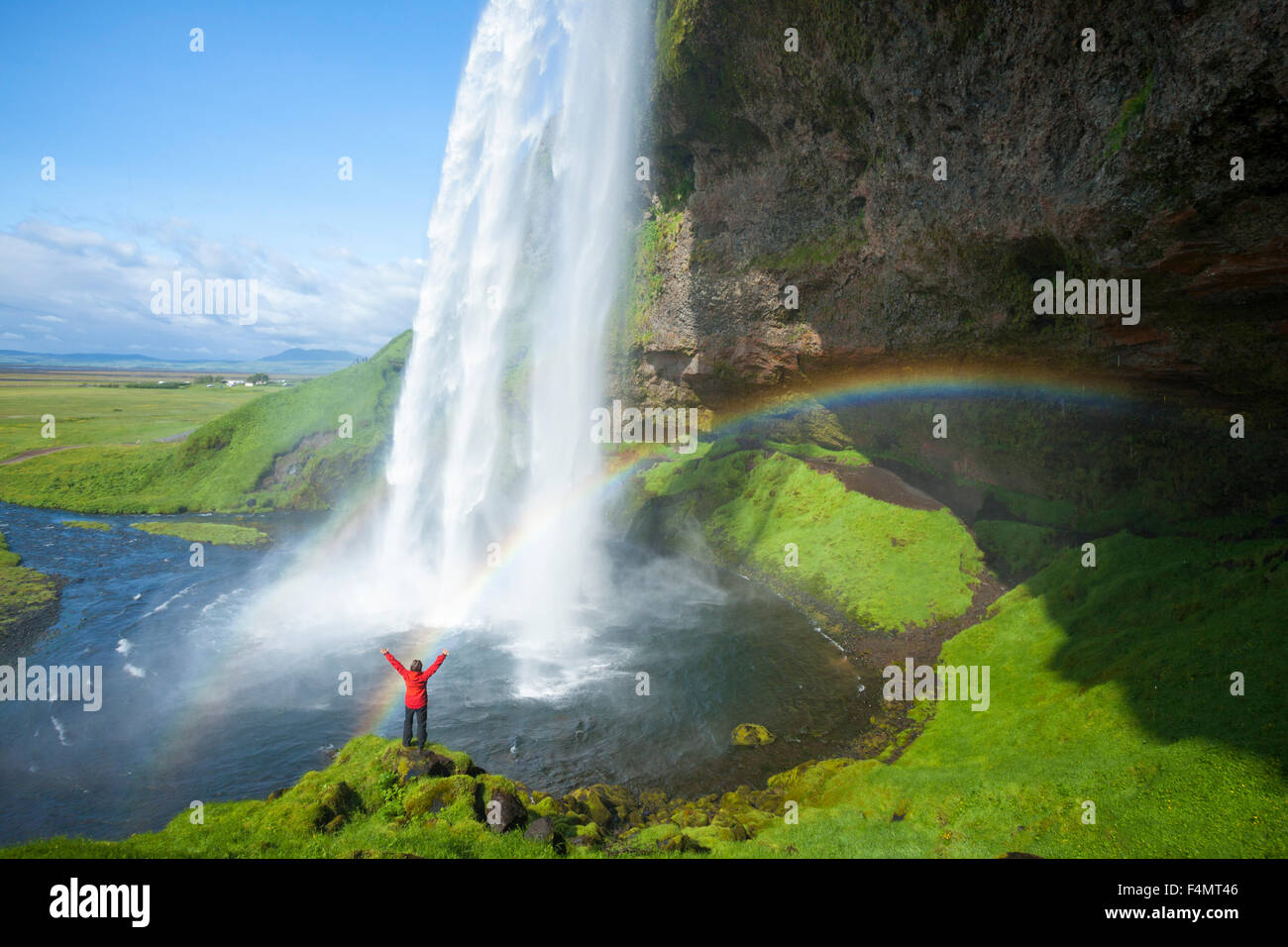 Person and rainbow beneath 60m-high Seljalandsfoss waterfall, Sudhurland, Iceland. Stock Photo