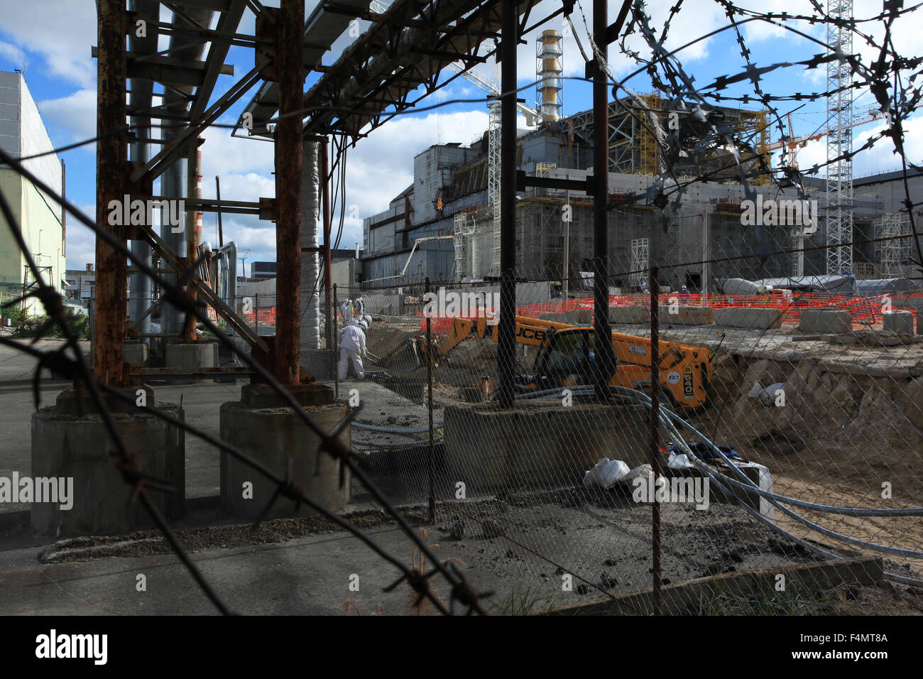 People working between the wrecked reactor no. 4 and the New Safe Confinement at the ChNPP construction site. Ukraine - Stock Image