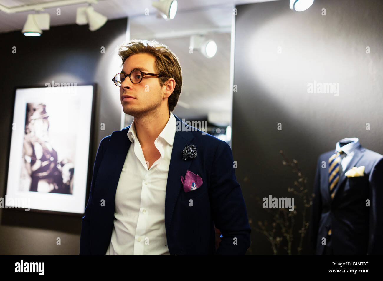 Thoughtful male designer standing in showroom - Stock Image