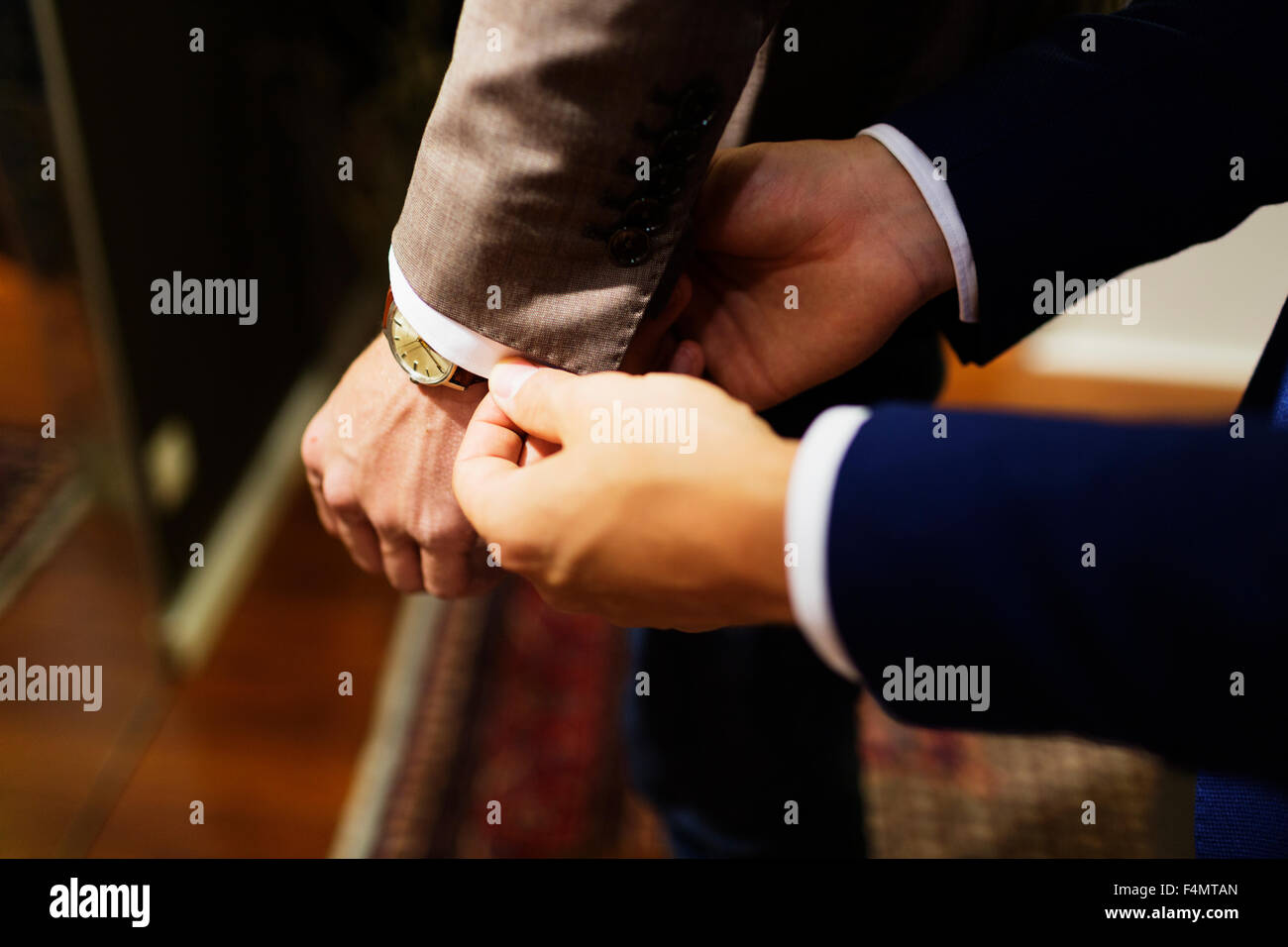 Cropped hands of sales clerk adjusting customer's sleeve in clothing store - Stock Image