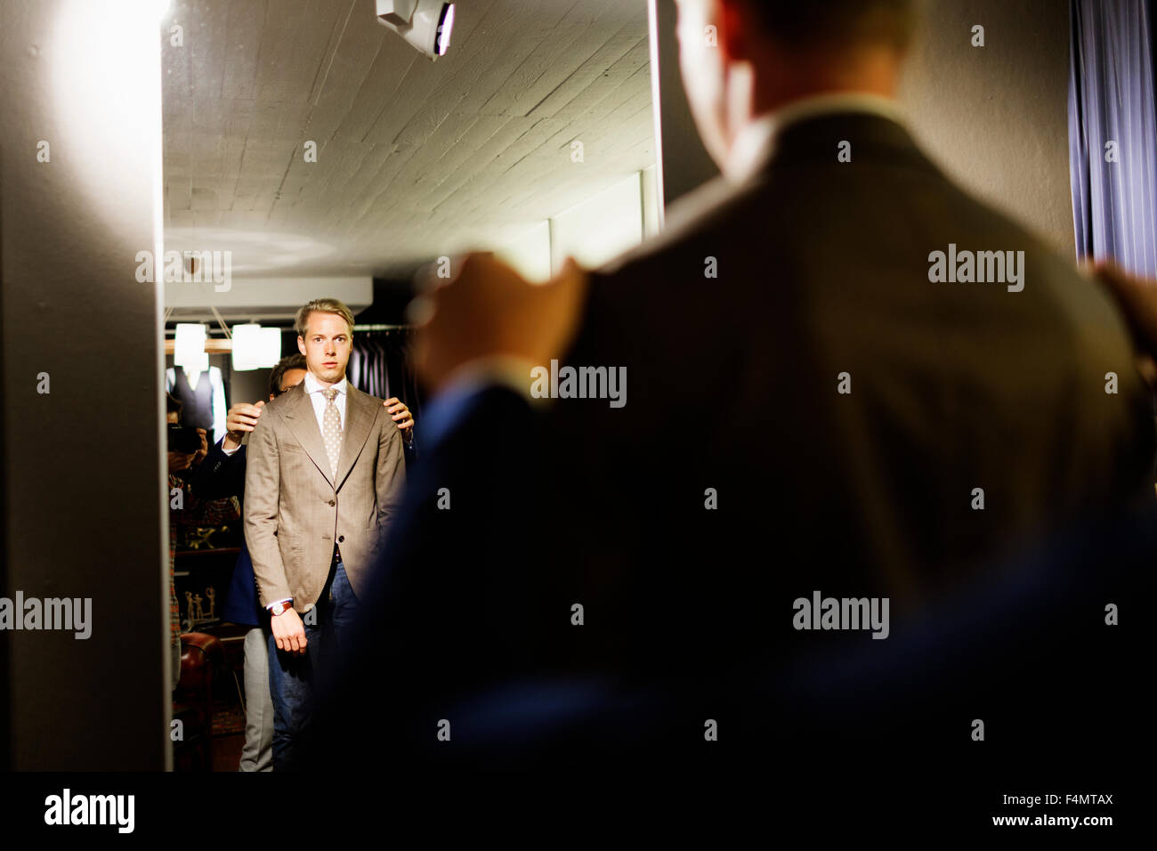 Sales clerk analyzing customer's suit in front of mirror at clothing store - Stock Image