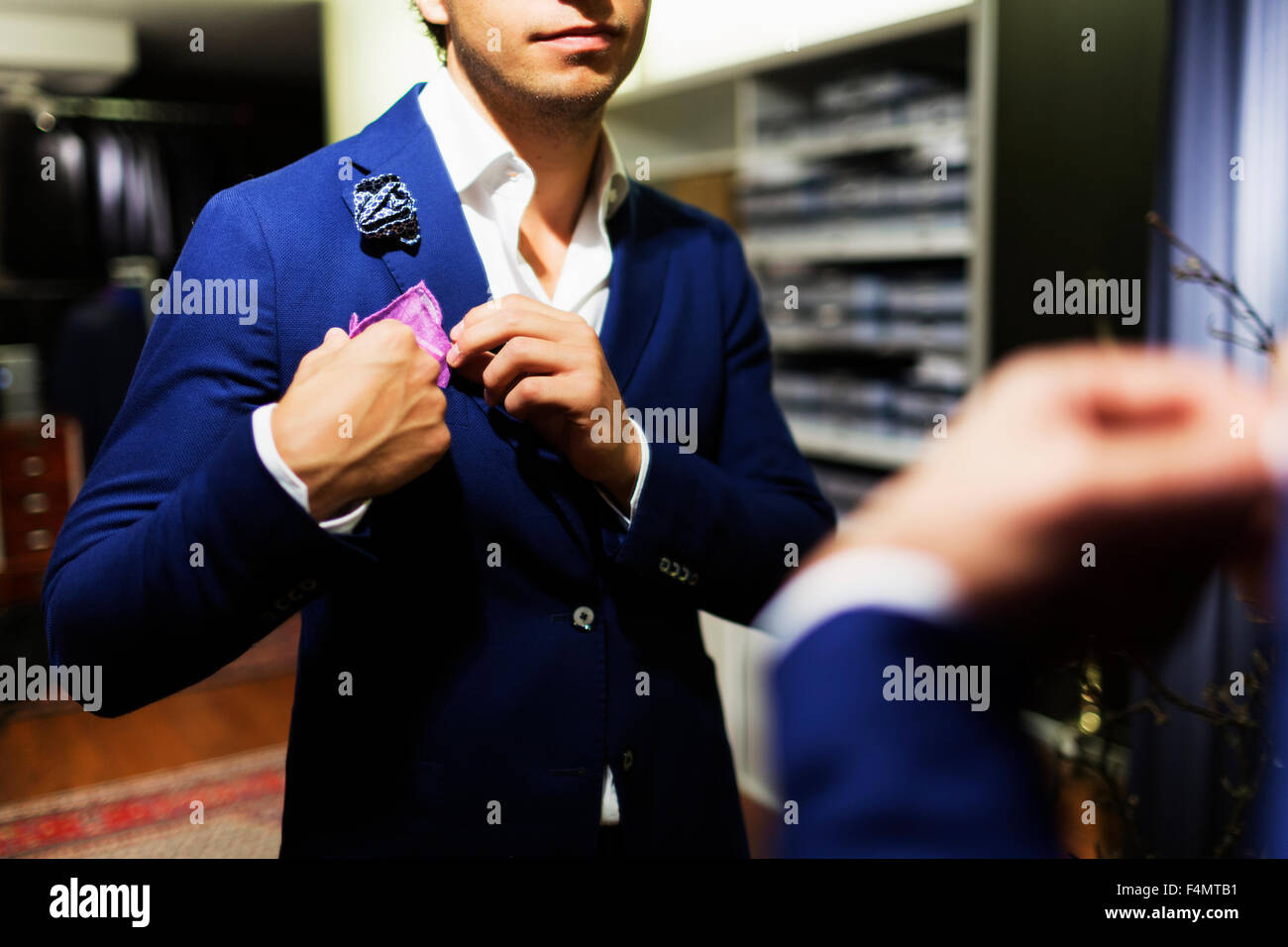Midsection of male customer adjusting handkerchief on suit at clothing store - Stock Image