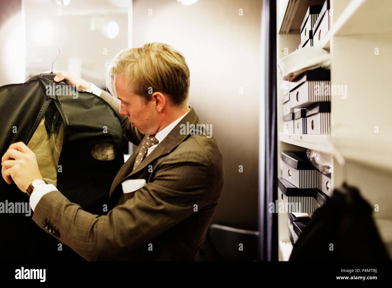 Sales clerk examining suit by shelves in clothing store - Stock Image