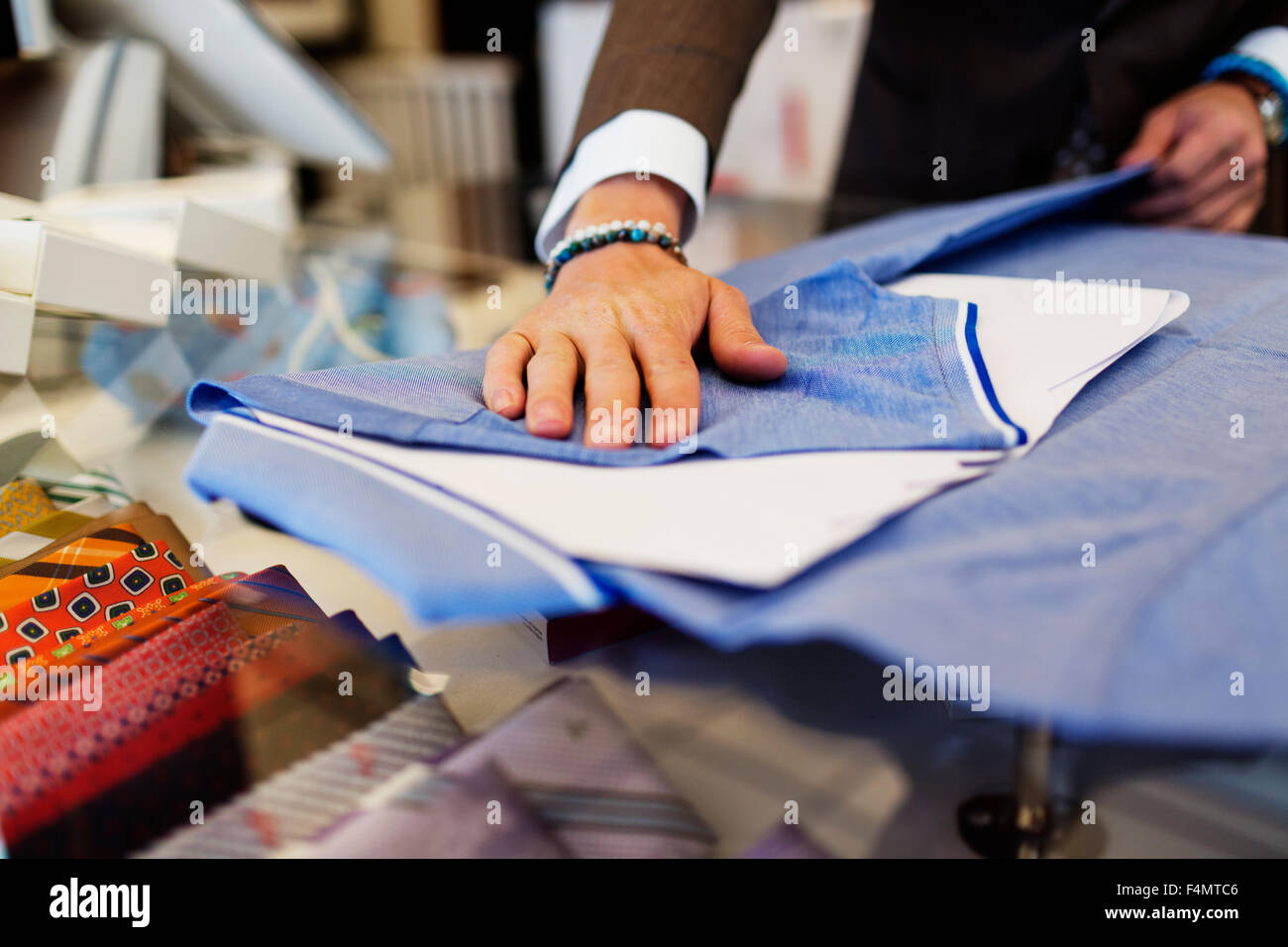 Sales clerk folding t-shirt on table in clothing showroom - Stock Image