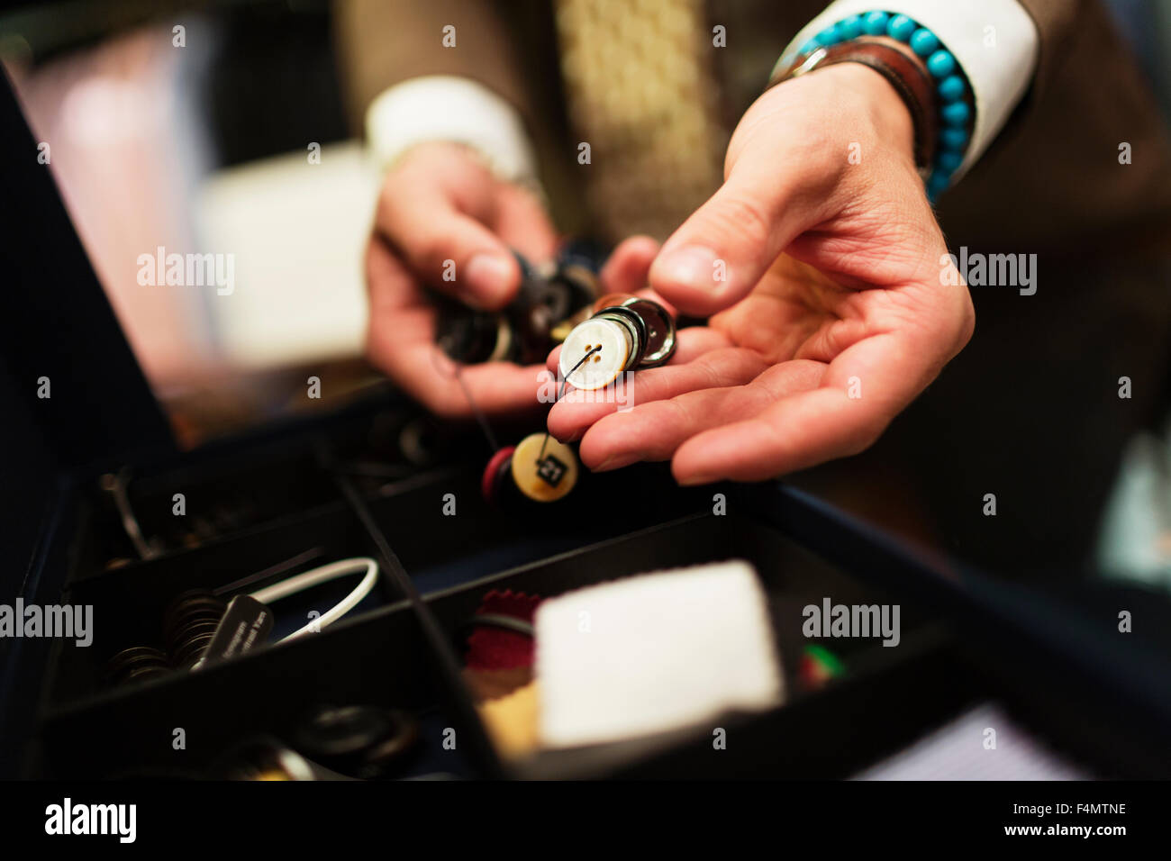 Close-up of fashion designer choosing buttons in drawer - Stock Image