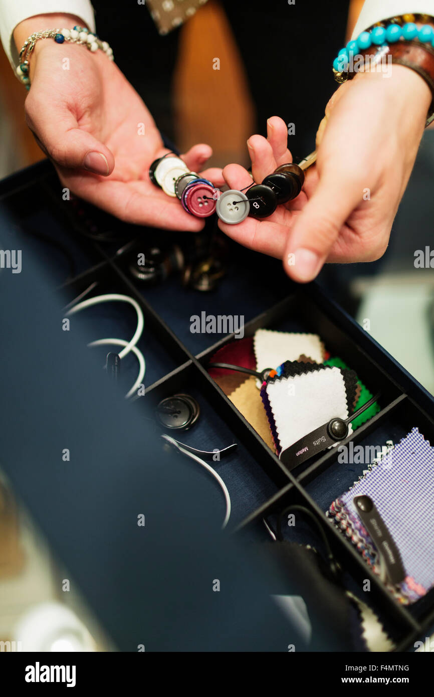 High angle view of fashion designer choosing buttons in drawer - Stock Image