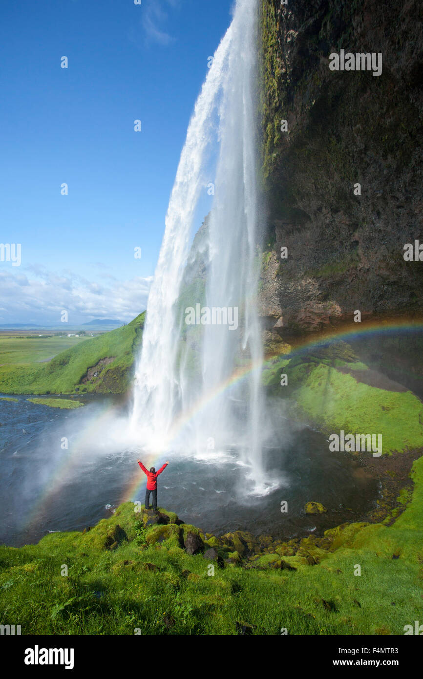 Person and rainbow beneath 60m-high Seljalandsfoss waterfall, Sudhurland, Iceland. - Stock Image