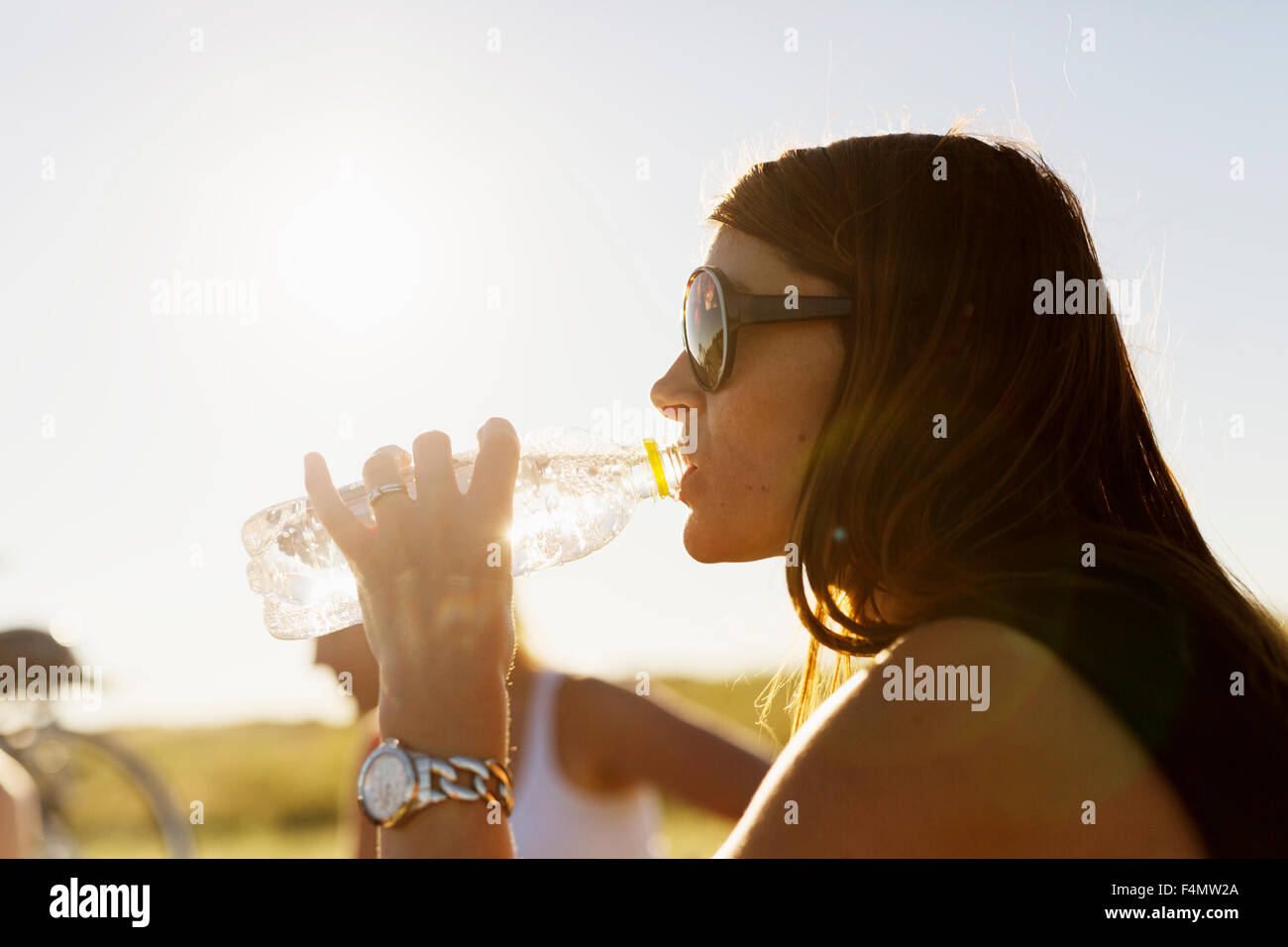 Close-up of woman drinking water from bottle at park - Stock Image