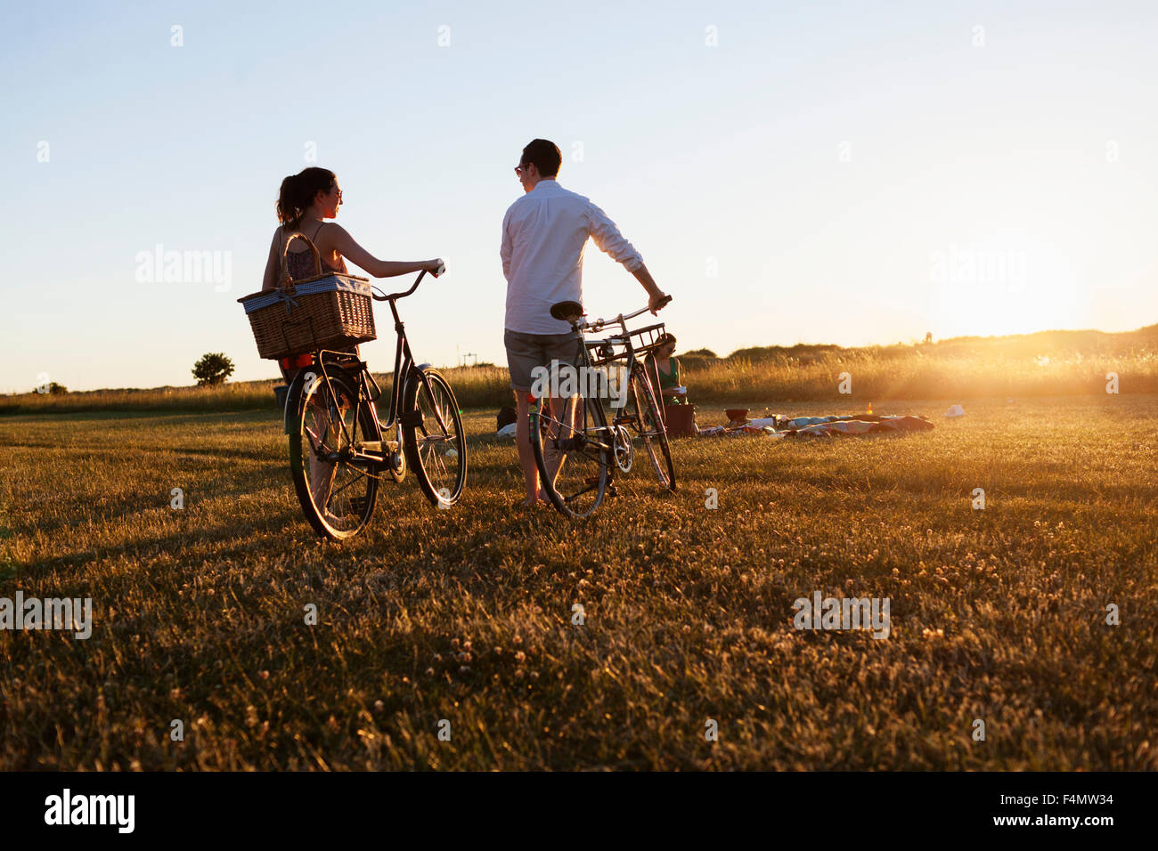 Rear view of friends walking with bicycle on field - Stock Image