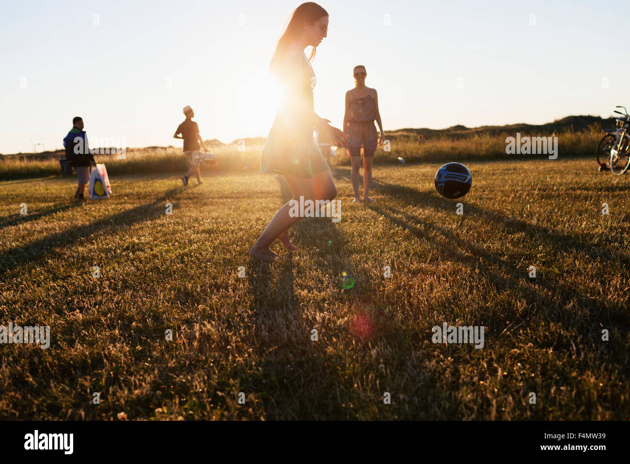 Friends playing football on field during sunset Stock Photo