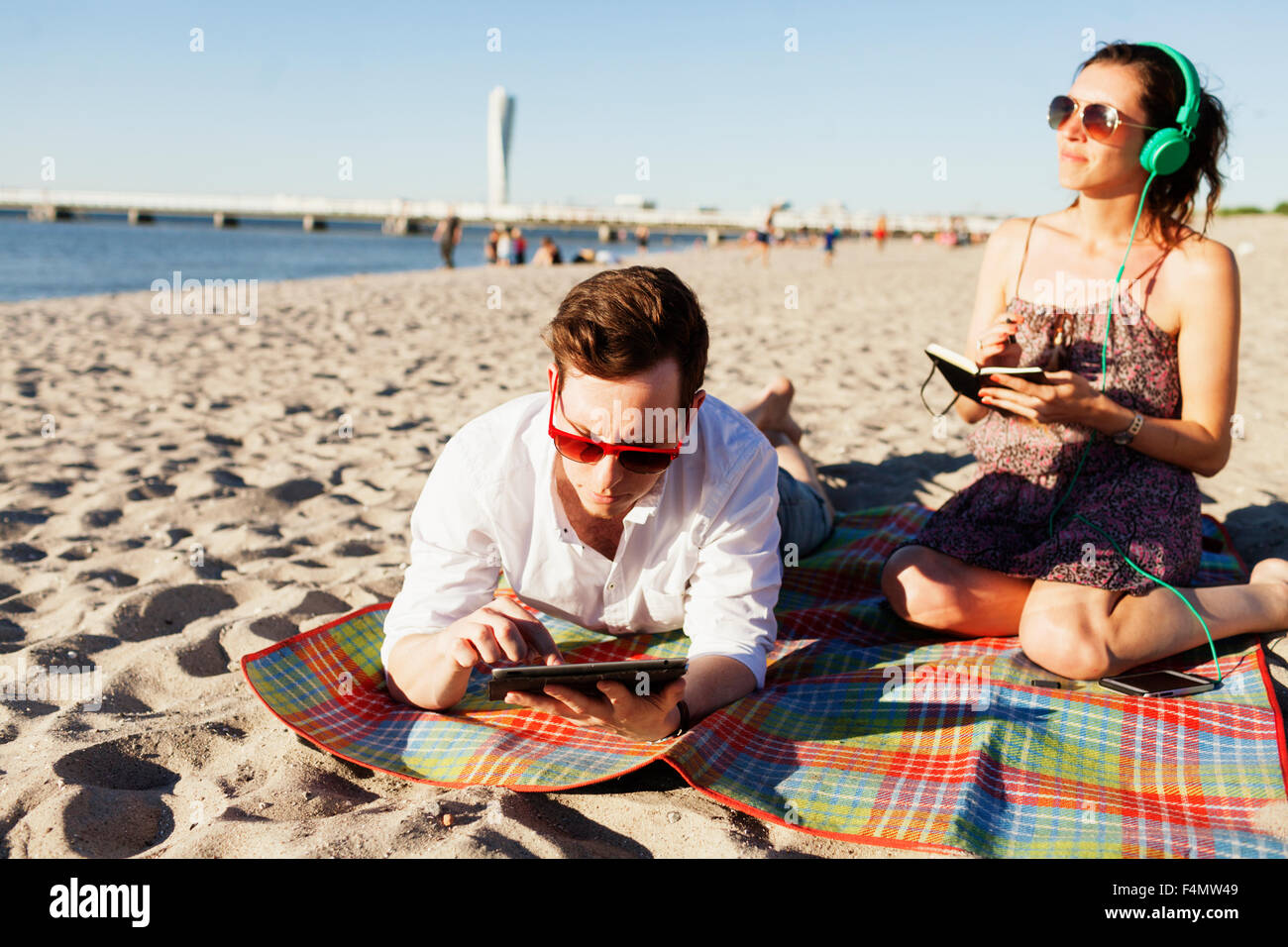 Man using digital tablet and thoughtful friend listening music at beach - Stock Image