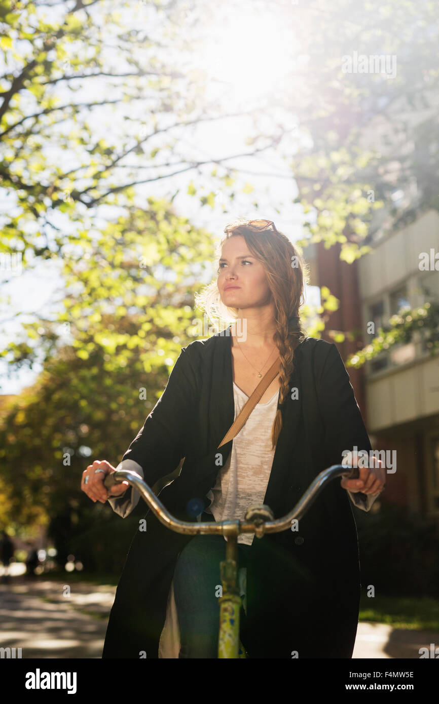 Beautiful young woman riding bicycle on city street Stock Photo