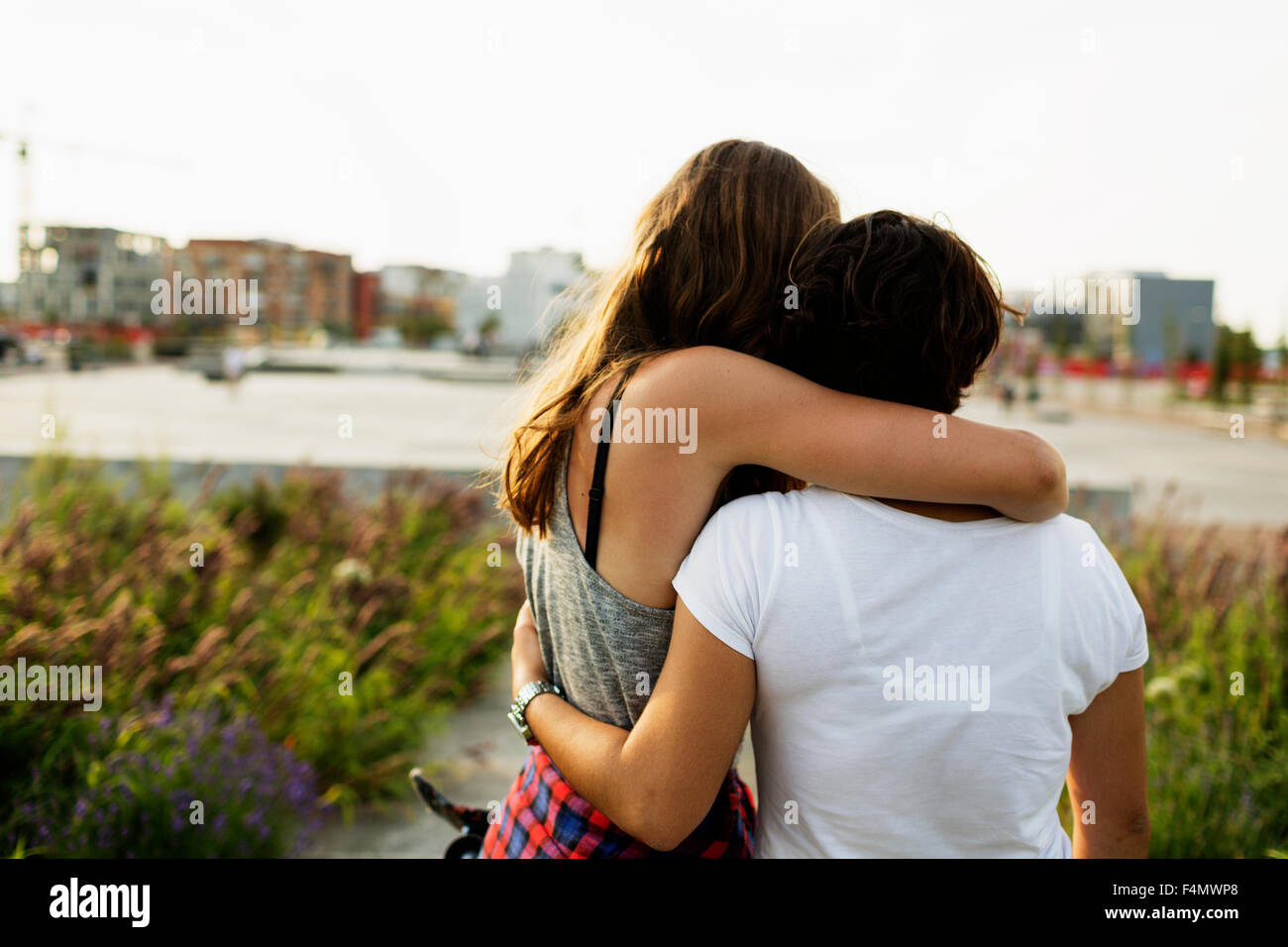 Rear view of female friends embracing at skateboard park - Stock Image