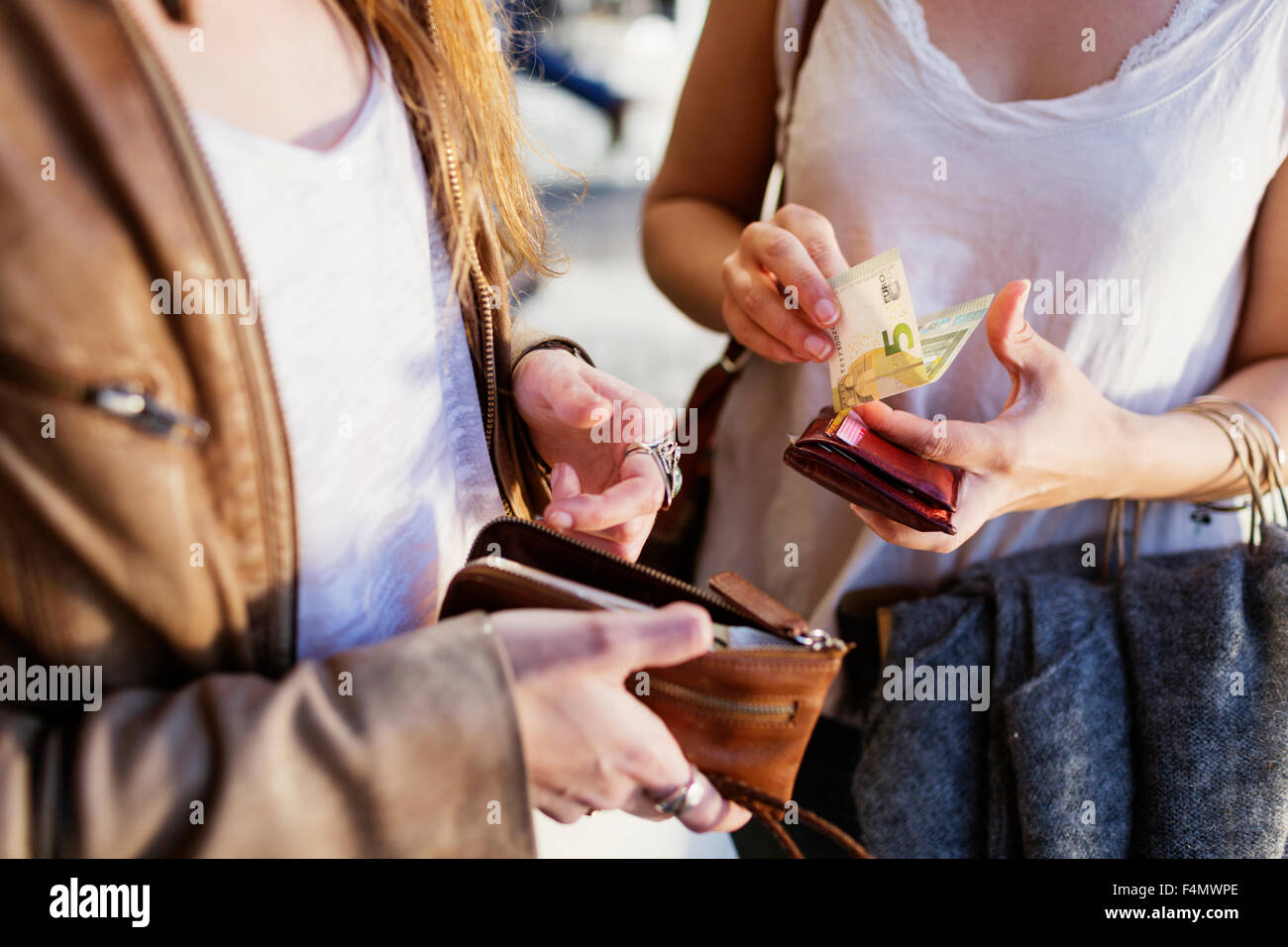 Midsection of shopaholic women holding 5 euro bill and wallets - Stock Image