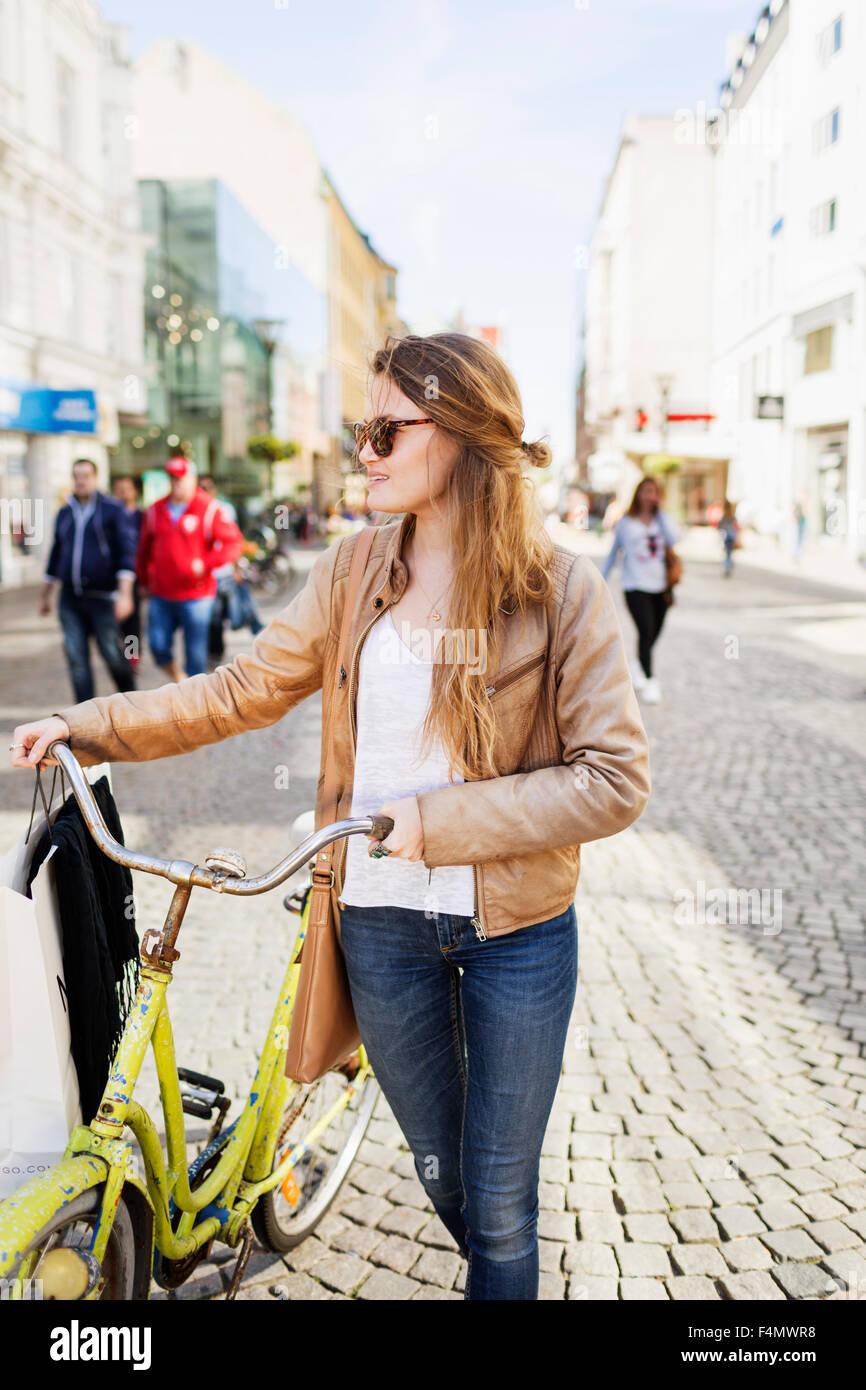 Beautiful shopaholic woman walking with bicycle on cobblestone street - Stock Image