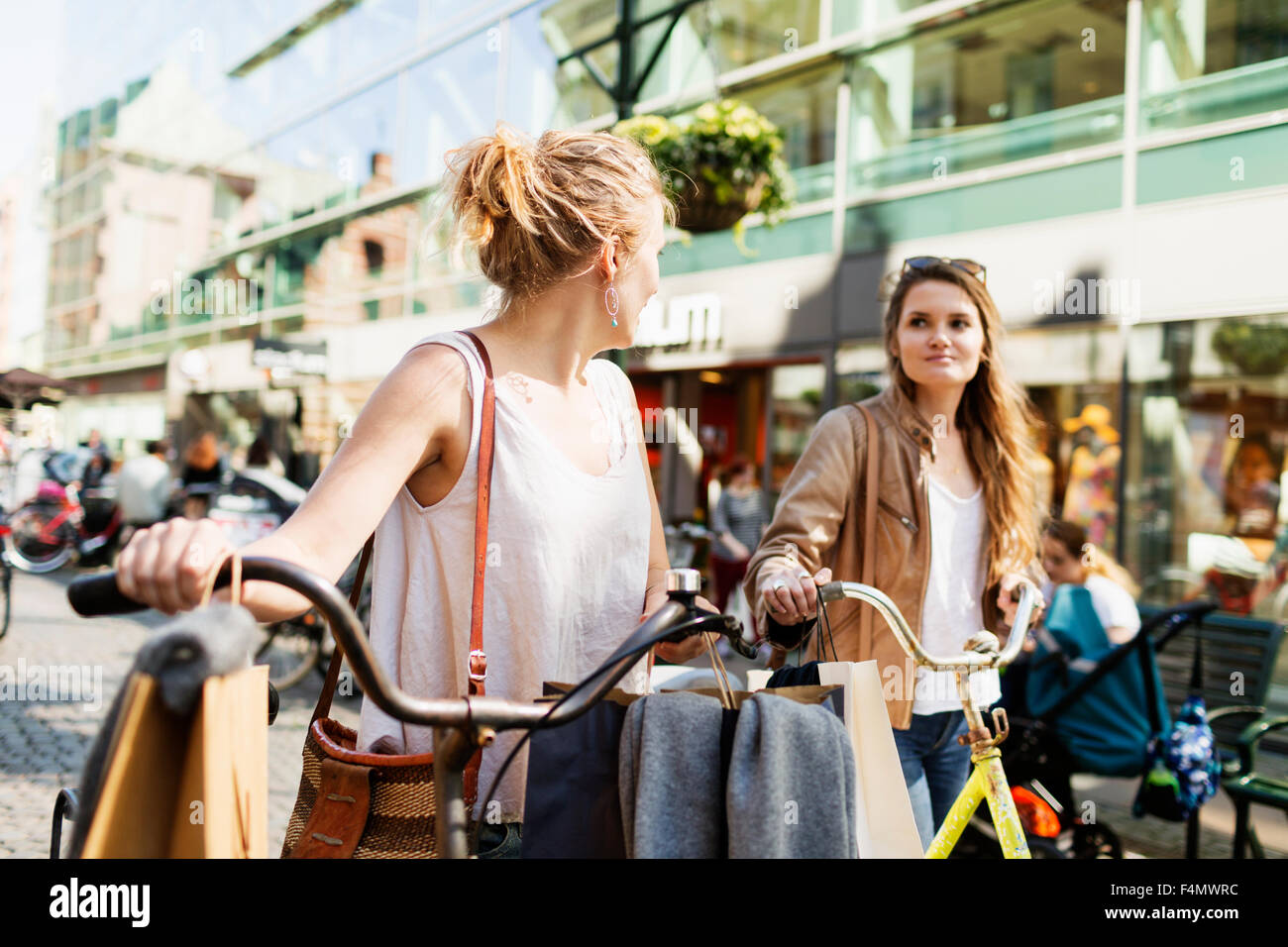 Beautiful friends with bicycle and shopping bags walking on city street - Stock Image