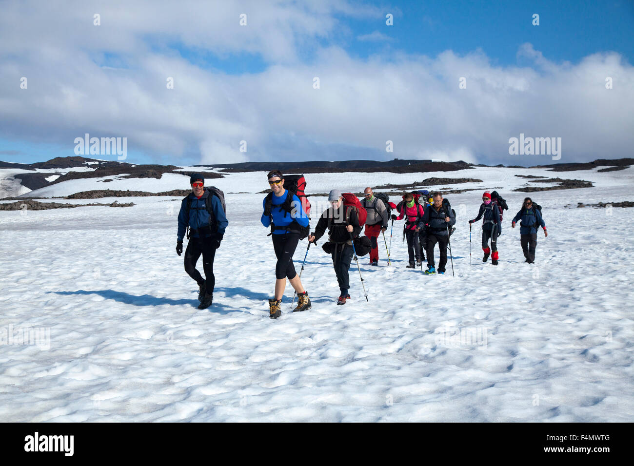 Hikers crossing snow on the Skogar to Fimmvorduhals trail, Sudhurland, Iceland. - Stock Image