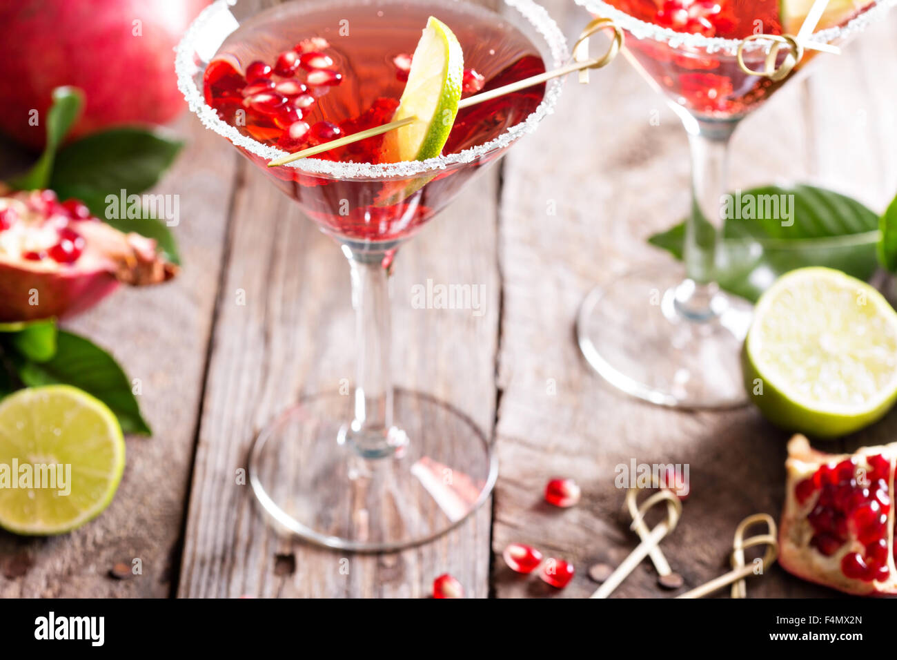 Pomegranate martini with slices of lime and pomegranate seeds - Stock Image