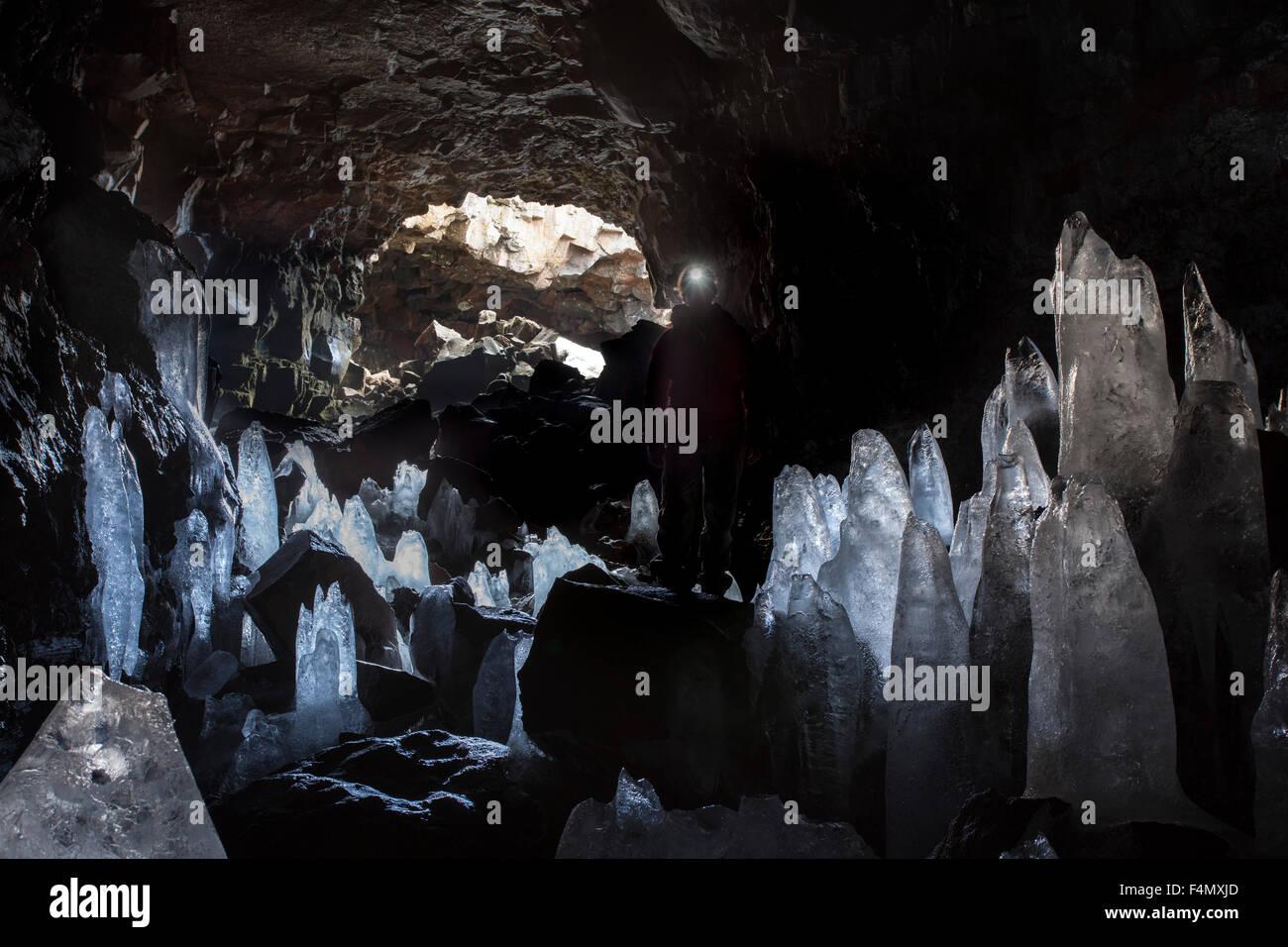 Person amongst ice stalagmites in Raufarholshellir lava tube, near Hveragerdi, Sudherland, Iceland. - Stock Image