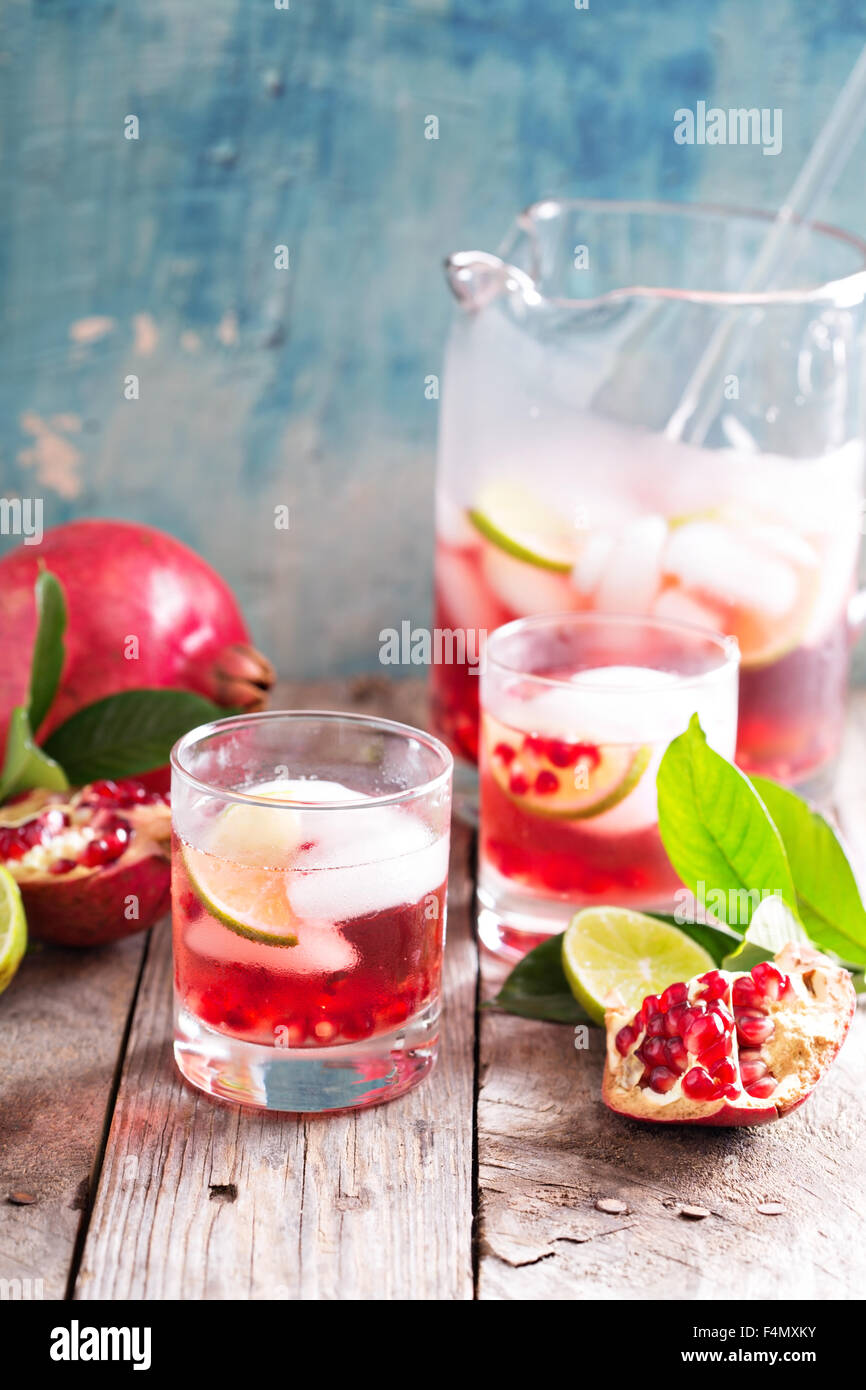 Pomegranate margarita cocktail with lime slices and ice - Stock Image