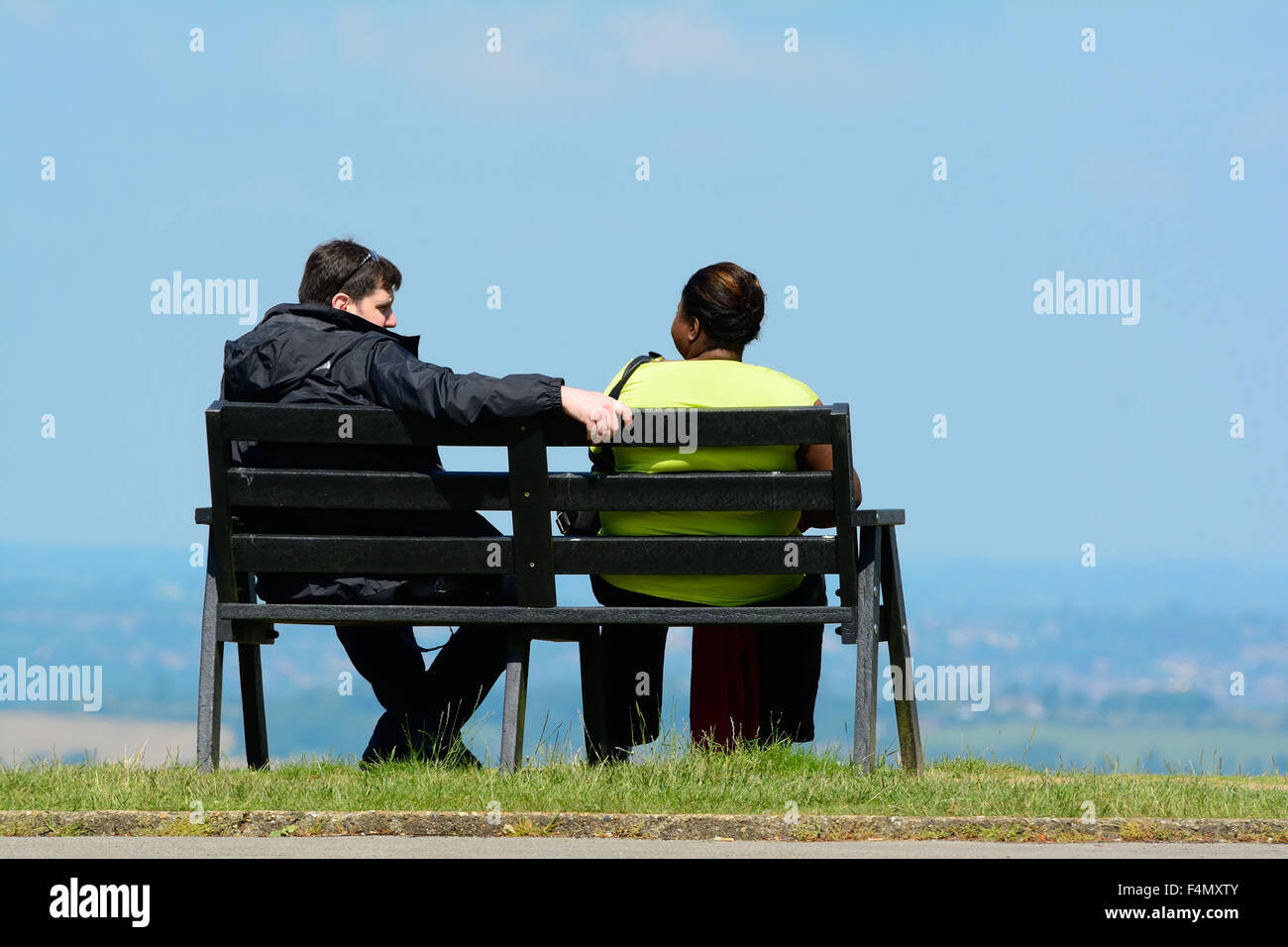 Caucasian man sitting on bench with Afro-Caribbean woman - Stock Image