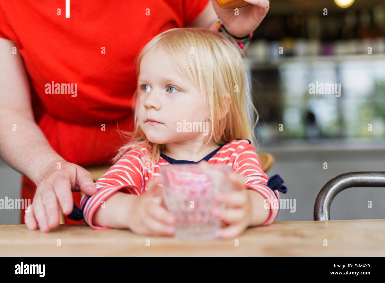Mother standing behind daughter holding drinking glass at cafe table - Stock Image