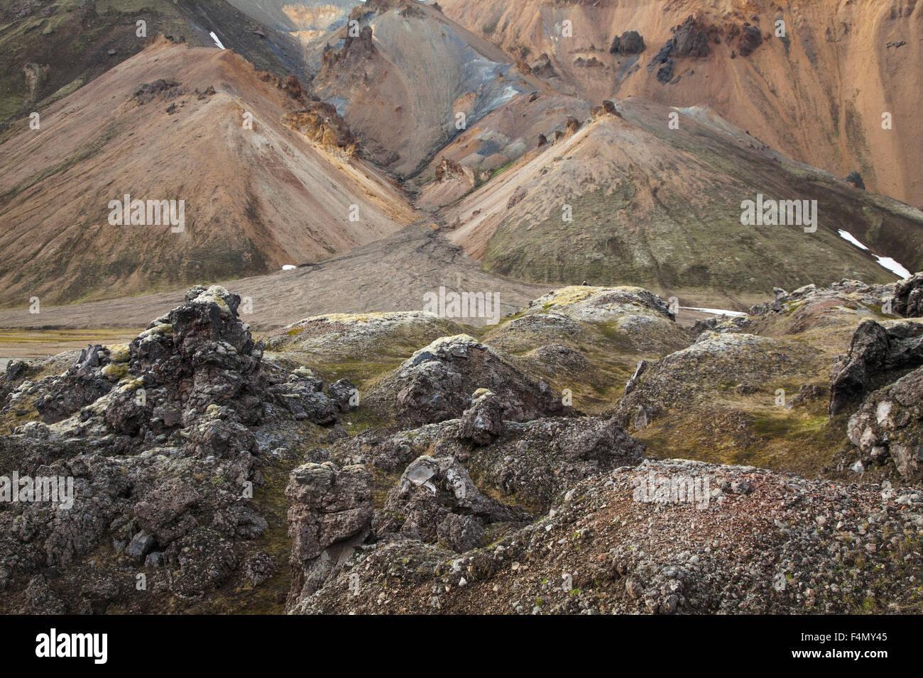 Lava field beneath rhyolite mountains, Landmannalaugar, Sudhurland, Iceland. - Stock Image