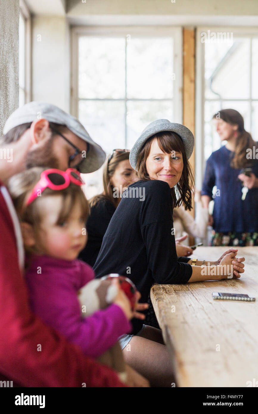 Smiling woman looking at family in restaurant - Stock Image