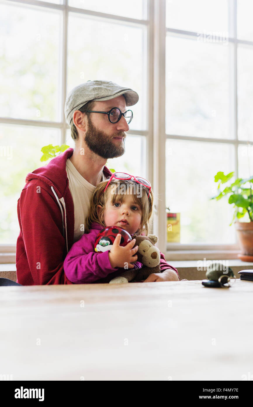 Portrait of daughter sitting with father in restaurant - Stock Image