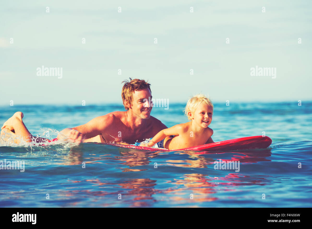 Father and son going surfing together. Summer fun outdoor lifestyle - Stock Image