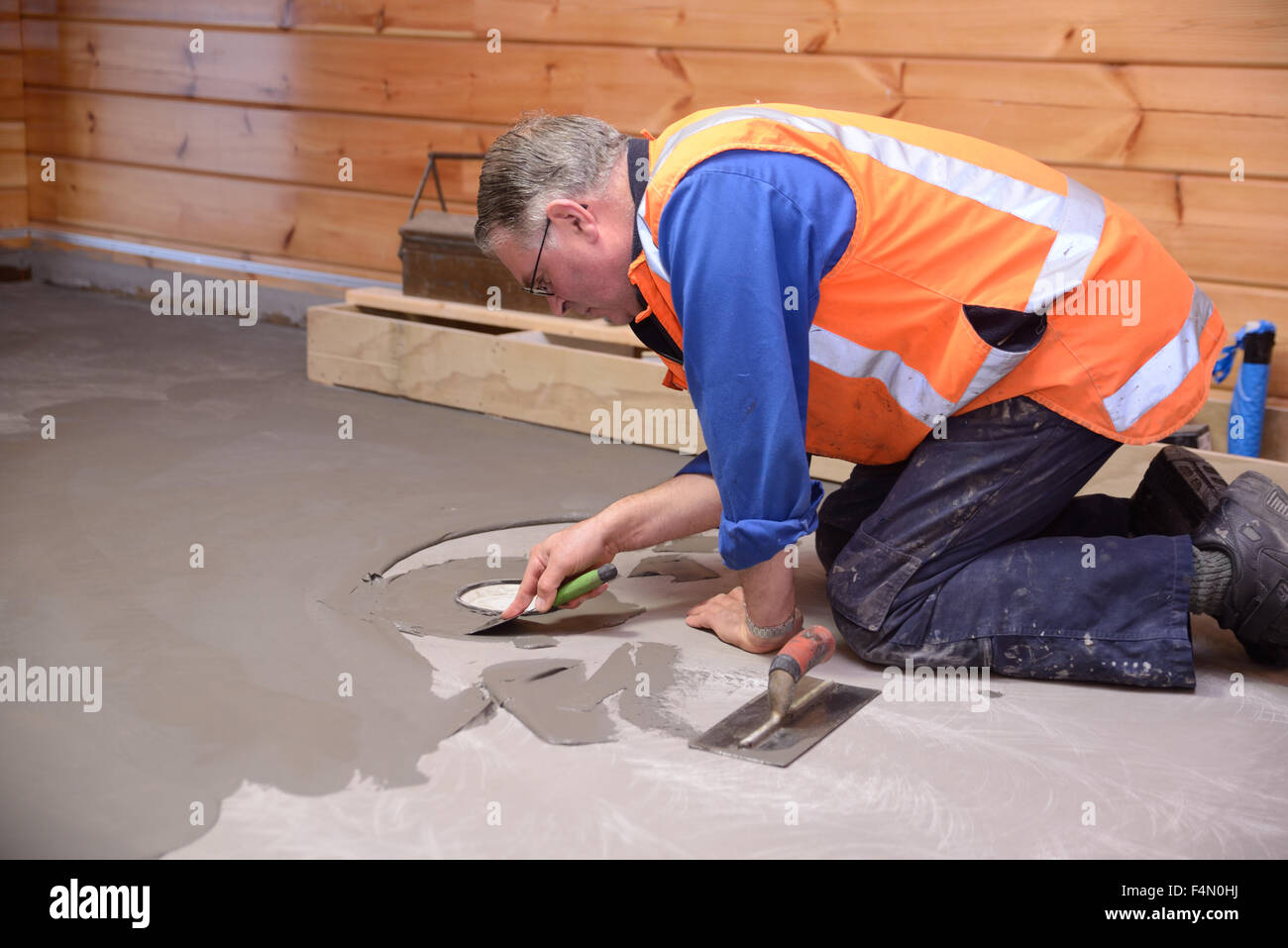 Tradesman Applying Leveling Compound To A Bathroom Floor Before - Leveling bathroom floor