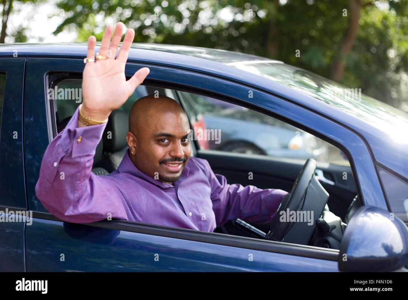 man waving goodbye from his car - Stock Image