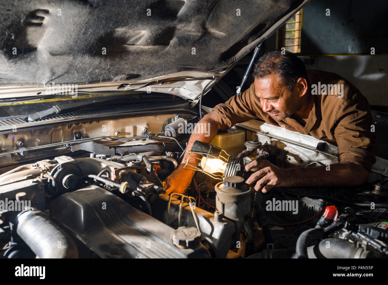 A car mechanic is repairing a german BMW car in a garage in the suburb Fort - Stock Image