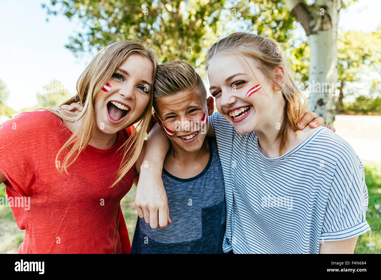 Austria, three teenagers with national colors painted on their cheeks celebrating together - Stock Image