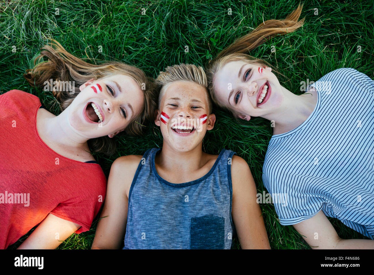 Austria, three teenagers with national colors painted on their cheeks lying on a meadow - Stock Image