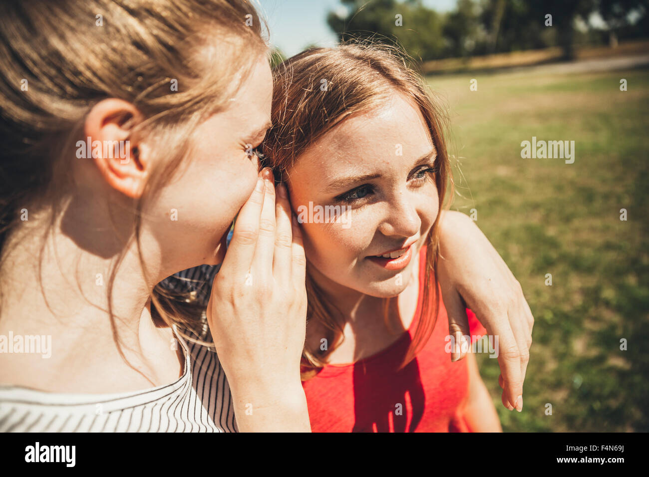 Two teenage girls whispering in park - Stock Image