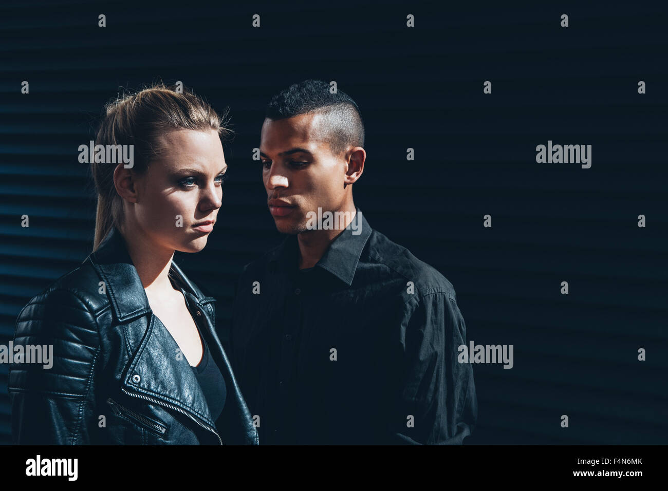 Black dressed young couple standing in front of black facade - Stock Image