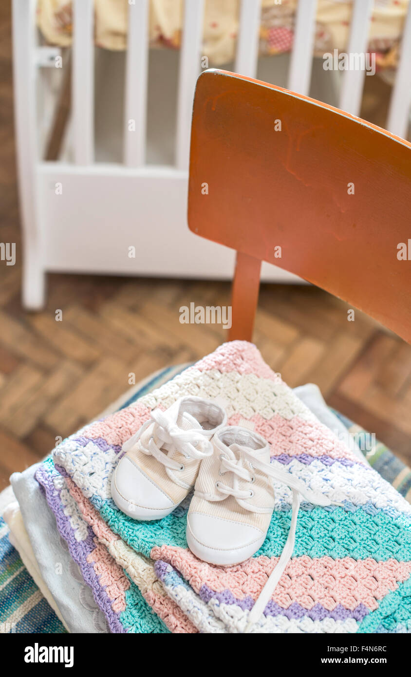 Stack of blankets and baby shoes on a chair - Stock Image