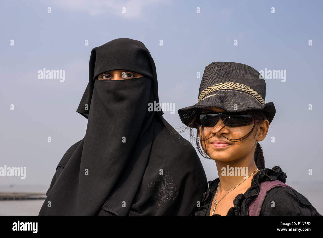 A portrait of two muslim women in contrast to each other, one dressed in the traditional black burka, hijab, and - Stock Image